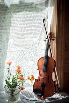 Violine mit noten und blumen auf fenstern.