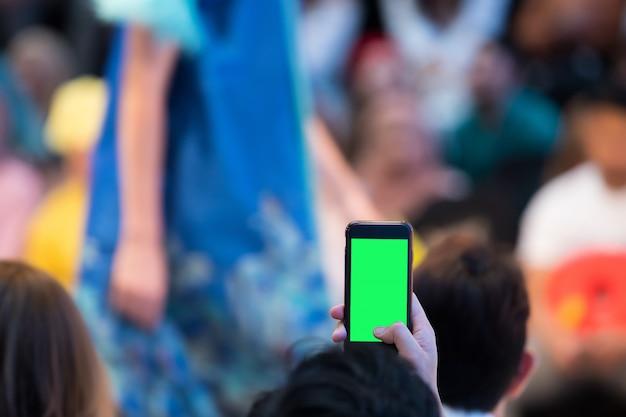 Vip-gäste aus der ersten reihe filmen die vdo-modenschau mit ihrem smartphone