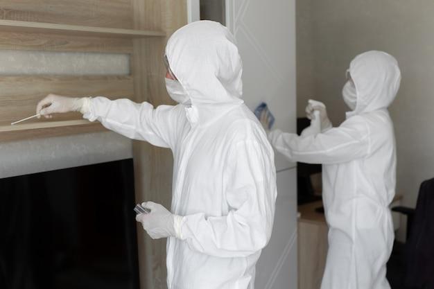 Virologen, menschen in schutzanzügen führen die desinfektion in der wohnung durch. wischen sie möbel ab und entnehmen sie während einer coronavirus-epidemie proben auf kontamination von der oberfläche. covid-19
