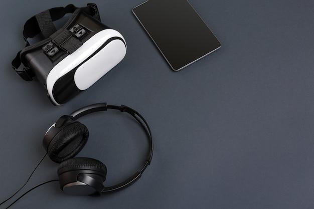 Virtual-reality-brille und tablet mit kopfhörern auf grauer hintergrundansicht von oben