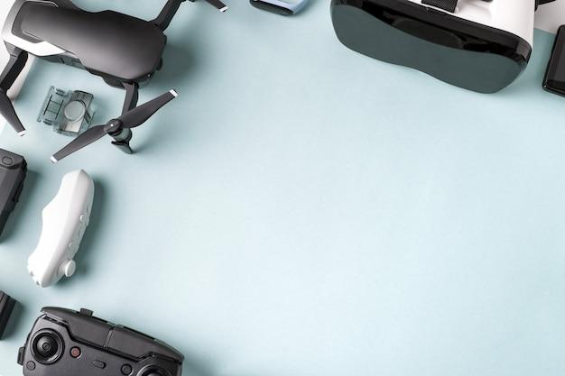 Virtual-reality-brille (vr) und eine drohne in der nähe ihres zubehörs auf blauem hintergrund mit platz für text
