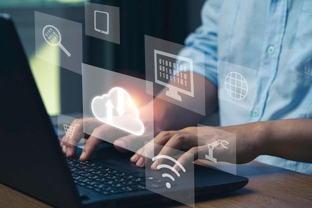 Virtuelle cloud- und technologie-symbole, geschäftsmann, der laptop-computer verwendet, um operationen durch cloud-computing-system zu steuern.