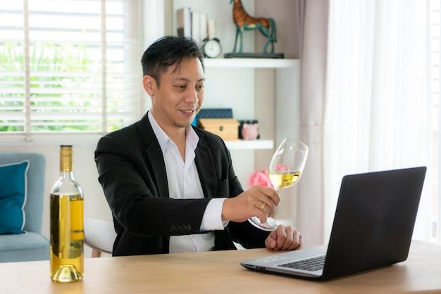 Virtuelle happy hour meeting-party des asiatischen mannes und das trinken des weißen traubenweins online zusammen