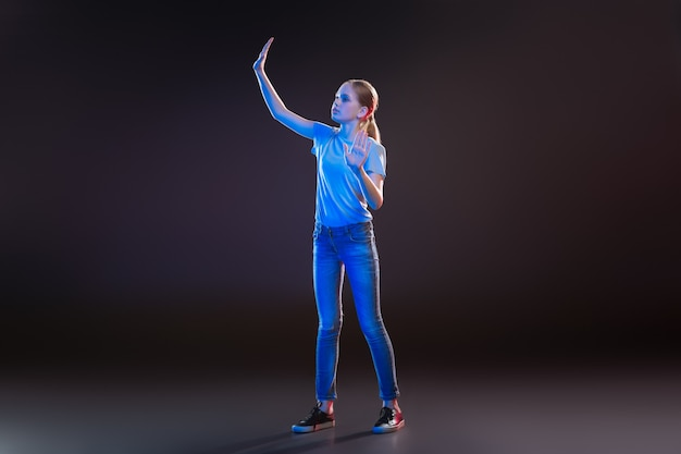 Virtuelle welt. hübsche junge frau mit transparenter technologie beim testen moderner entwicklungen