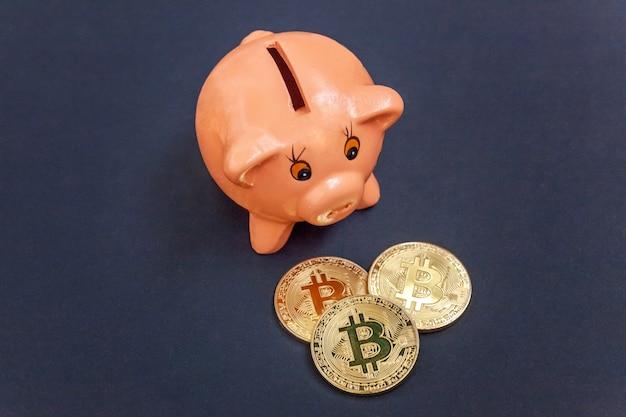 Virtuelles geld von sparschwein und goldener bitcoin-münze auf schwarzem hintergrund.