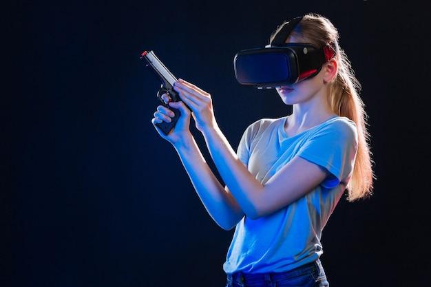 Virtuelles training. kluge blonde frau, die ihre waffe auflädt, während sie ein virtuelles training hat
