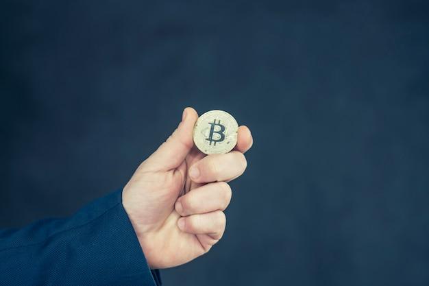 Virtuelles währungs- und blockchain-konzept. geschäftsmann in einer blauen jacke, die bitcoin in seinen händen hält.