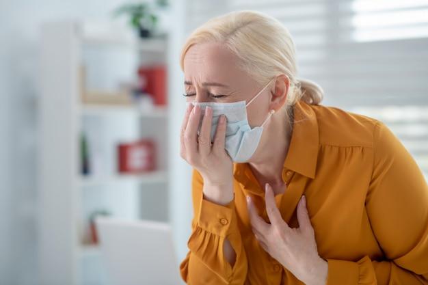Virus, husten. blondhaarige frau in einer gelben bluse in einer schützenden weißen maske, die sich an gesicht und brust festhält und sich krank fühlt