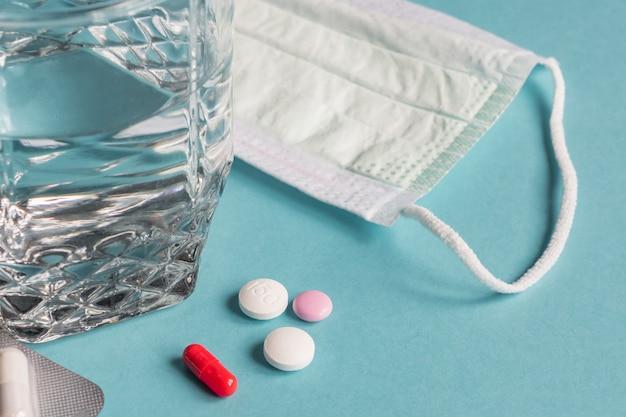 Virus-pandemie-behandlung. medizinmaske, pillen und glas wasser auf blauem hintergrund. coronavirus 2019, ncov