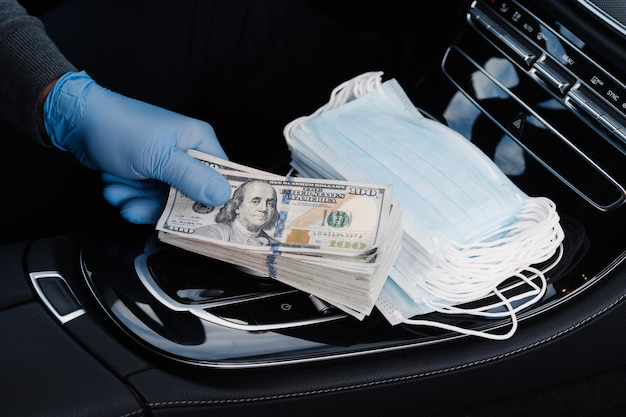 Viruskonzept. hand in gummihandschuhen hält stapel von dollar-banknoten, verdient geld, verkauft medizinische masken, posiert im auto. covid epidemie. spekulation auf dem markt über notwendige produkte. quarantäne zeitraum