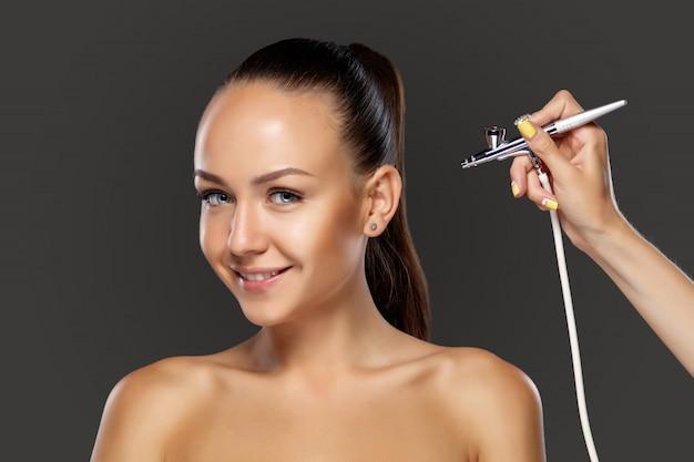 Visagist, der make-up für modell mit aerograph macht