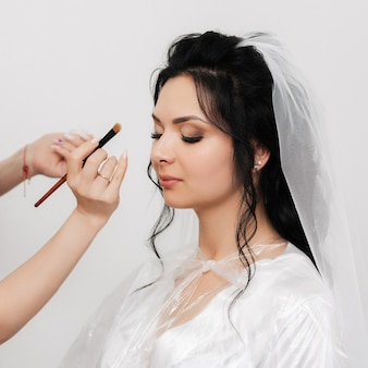 Visagisten hände mit einem pinsel schminken und schatten auf die augen des brautmädchens im schönheitssalon auftragen