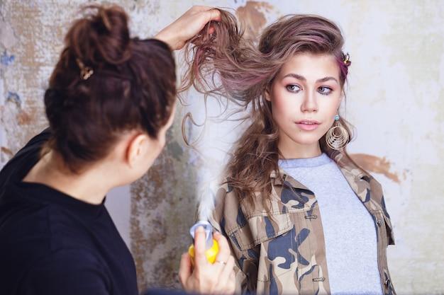 Visagistin, die haarspray auf das haar des modells aufträgt
