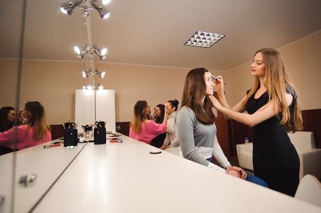 Visagistin, die professionelles make-up der jungen frau macht. schönheit shcool.