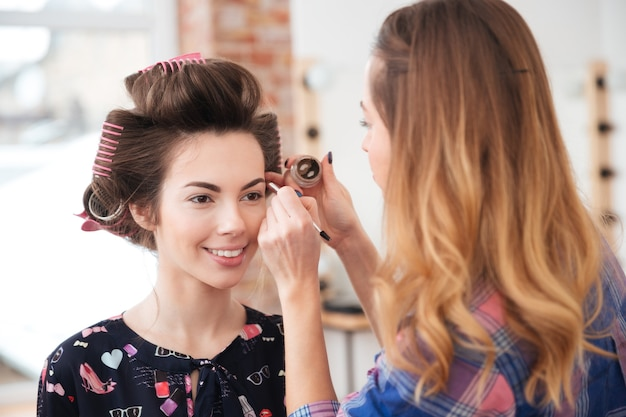 Visagistin, die professionelles make-up für ein glückliches süßes modell mit lockenwicklern im studio macht