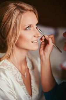 Visagistin macht make-up für junge schöne braut