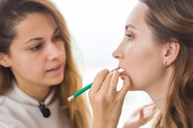 Visagistin macht professionelles make-up aus junger frau