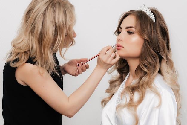 Visagistin malt die lippen einer braut mit einem lippenpinsel in einem professionellen schönheitssalon