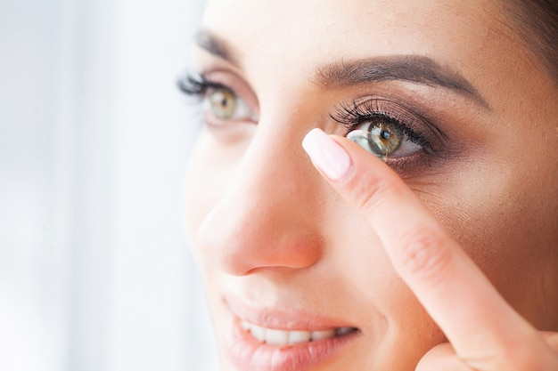 Vision-konzept. nahaufnahme geschossen von tragender kontaktlinse der jungen frau