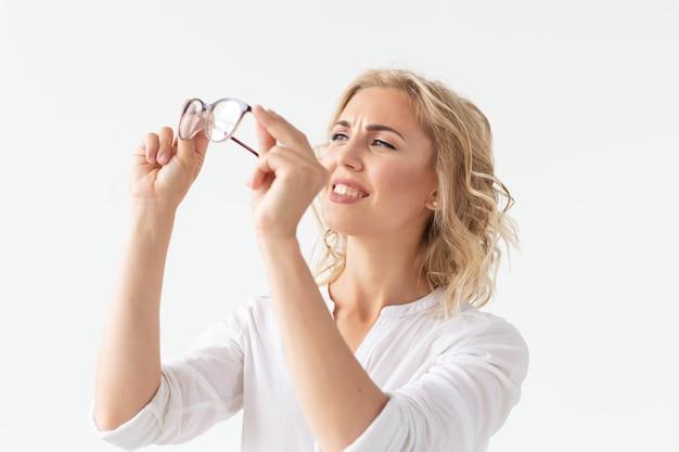 Vision, optik und schönheit - junge blonde frau, die eine brille auf weiße wand setzt.