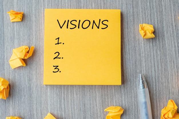 Visionswort auf gelber anmerkung zerbröckelte papier auf holztisch