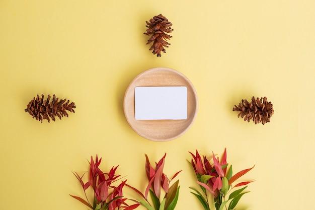 Visitenkarte auf holz mit kiefer-blumen auf pastellgelbem hintergrund. minimalistischer stil