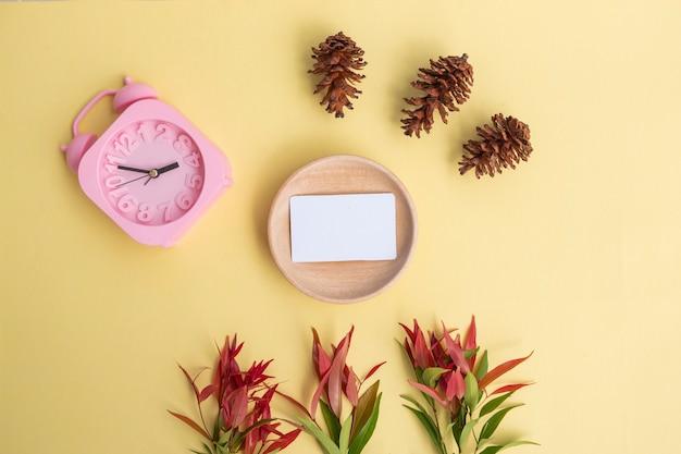 Visitenkarte auf holz mit kiefer-blumen und wecker auf pastellgelbem hintergrund. minimalistischer stil