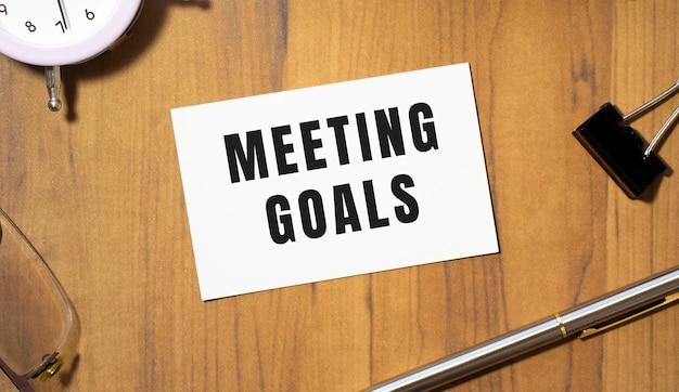 Visitenkarte mit dem text meeting goals liegt auf einem hölzernen bürotisch