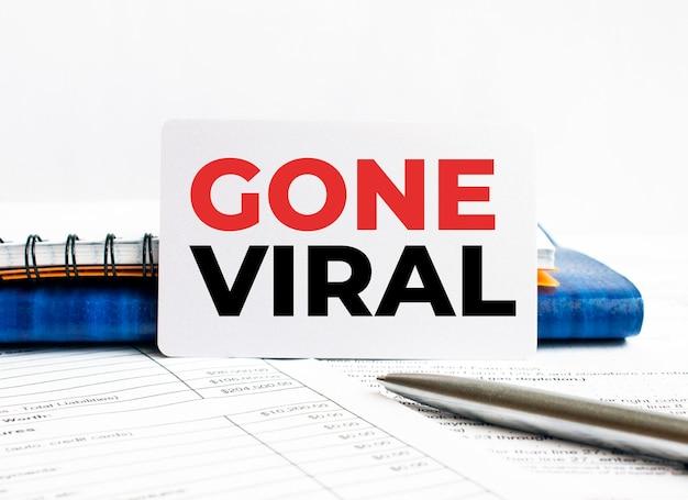 Visitenkarte mit text gone viral liegend auf blauem notizbuch.