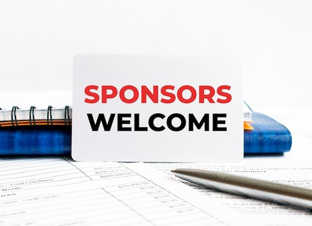 Visitenkarte mit text sponsoren willkommen auf blauem notizbuch liegen