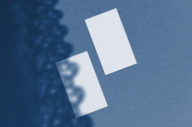 Visitenkarte mockup. natürliches überlagerungslicht beschattet die blätter. visitenkarten im format 3,5 x 2 zoll. szene der blattschatten. klassische blaue farbe. farbe des jahres 2020.