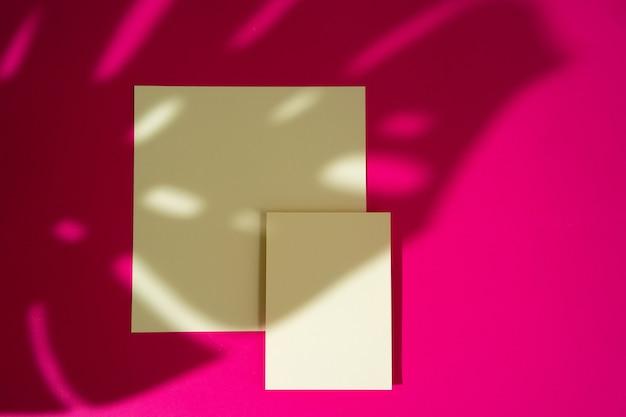 Visitenkarten auf rosa hintergrund mit laubschatten