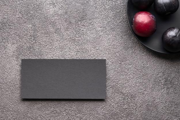 Visitenkarteneinladung schwarze postkarte auf grauem beton flach legen pflaumen dunkler schlüssel eine stilvolle einladung...
