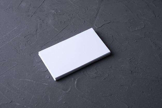 Visitenkartenrohling auf beton rock hintergrund. firmenbriefpapier, branding-modell. kreativer designer-schreibtisch. flach liegen. kopieren sie platz für text. vorlage für id.