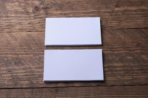 Visitenkartenrohling auf hölzernem hintergrund. firmenbriefpapier, branding-modell. kreativer designer-schreibtisch. flach liegen. kopieren sie platz für text. vorlage für id.