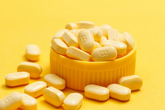 Vitamin b tabletten auf gelbem hintergrund