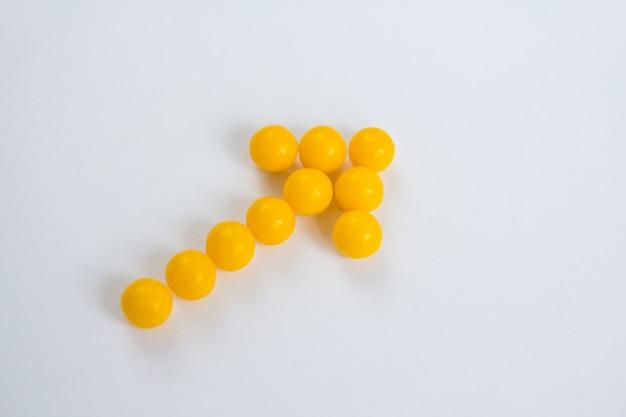 Vitamin c-kapseln in form von pfeil auf weißem hintergrund