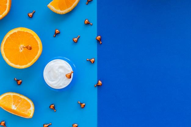 Vitamin c, natürliche anti-aging-kosmetik-cremeflasche und serumampulle mit zitrusfrüchten. hautpflege-kosmetikprodukt mit vitaminen. gesichtshaut revitalisierende, heilende kapseln mit natürlichem öl.