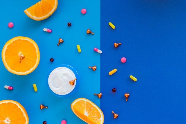 Vitamin c, natürliche anti-aging-kosmetikcremeflasche und serumampulle mit zitrusfrüchten. hautpflegekosmetik für frauen mit vitaminen. gesichtshaut revitalisierende, heilende kapseln mit natürlichem öl.