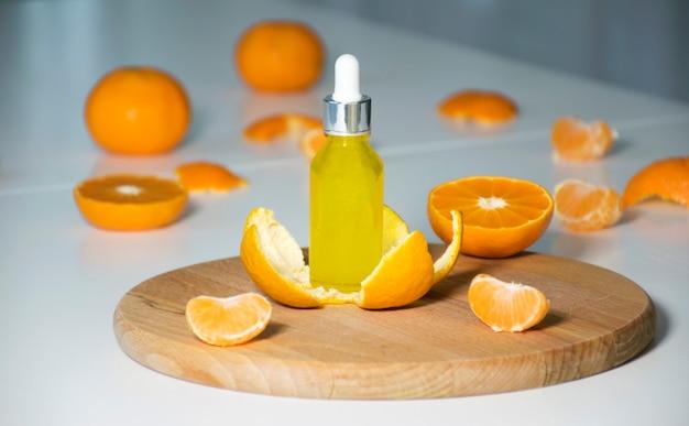 Vitamin c-serum in kosmetikflasche in mandarinenschale mit mandarinen auf hintergrund. ätherisches zitrusöl, gesichtspflege, bio-spa-kosmetik mit pflanzlichen inhaltsstoffen.