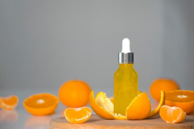 Vitamin c serum kosmetikflasche in mandarinenschale mit orangefarbenen stücken auf grauem hintergrund mit kopienraum.