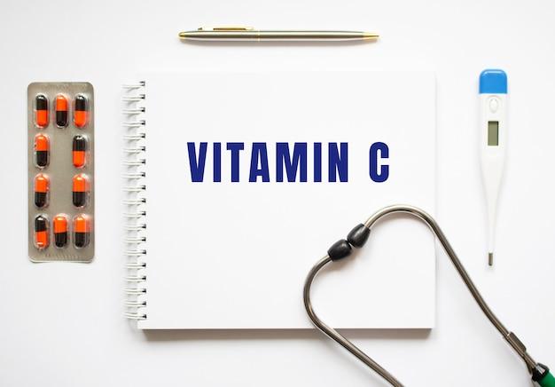 Vitamin c steht in einem notizbuch auf einem weißen tisch neben pillen und einem stethoskop. medizinisches konzept
