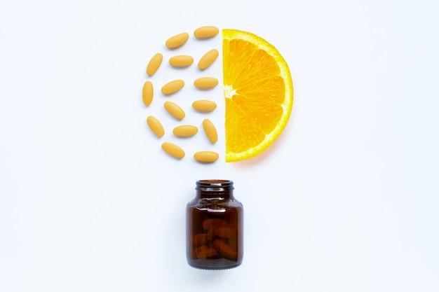 Vitamin- cflasche und -pillen mit orange frucht auf weiß