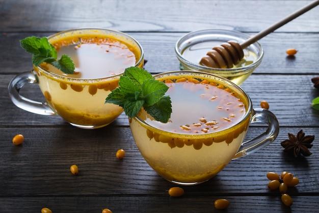 Vitamin gesunder sanddorn-tee in glasbechern mit frischen rohen sanddornbeeren und zimtstangen, anissternen, minze und honig auf einem dunklen küchentisch.