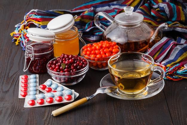Vitamin-gesunder sanddorn-tee in kleiner glasteekanne mit frischen rohen sanddornbeeren und honig, volksmedizin