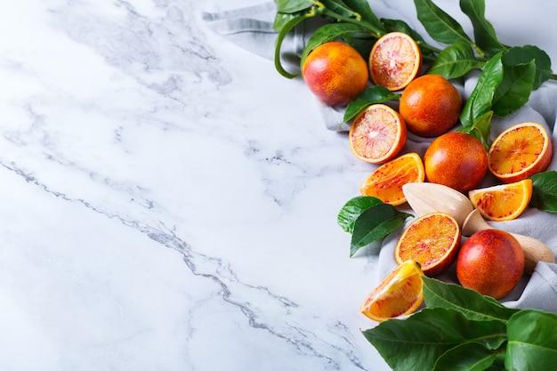 Vitamin, sauberes essen, veganes konzept für gesundes essen. ganze und geschnittene süße sizilianische blutorangen auf einem weißen marmortisch. draufsicht flach kopieren raumhintergrund