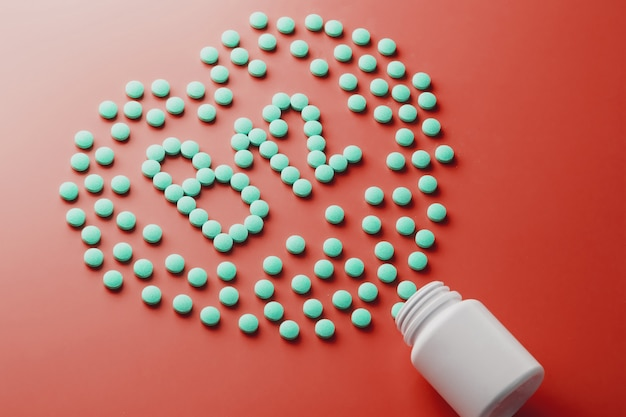 Vitamine b 12 in form eines herzens auf rotem untergrund, ausgegossen aus einem weißen glas.