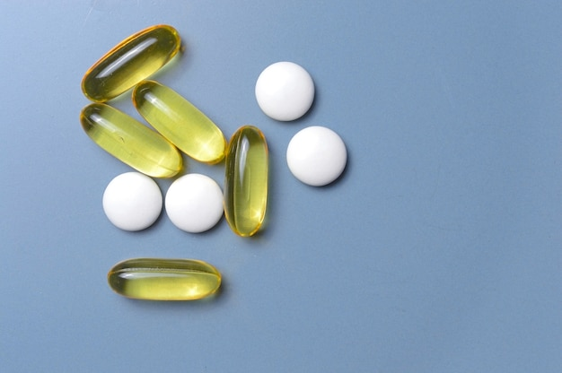 Vitamine in kapseln und tabletten auf grauem hintergrund. ansicht von oben