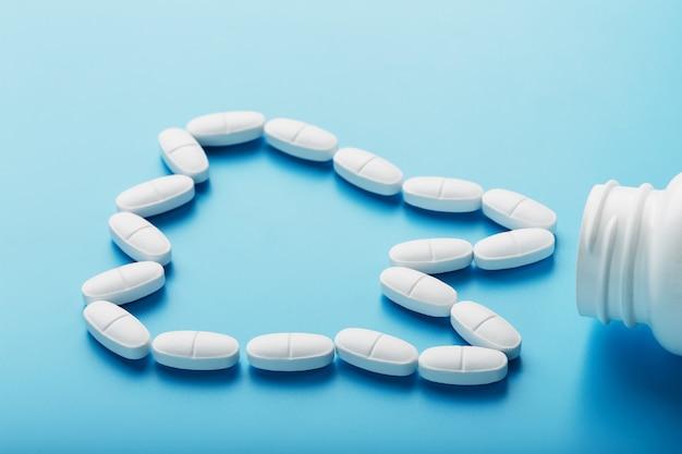 Vitamine mit kalzium in form eines zahnes wurden aus einem weißen glas auf einem blauen hintergrund heraus verschüttet