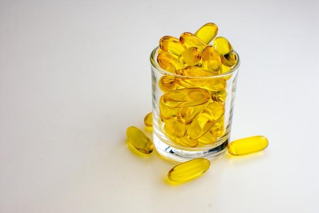 Vitamine oder fischölkapsel auf kleinem glas und klarem hintergrund